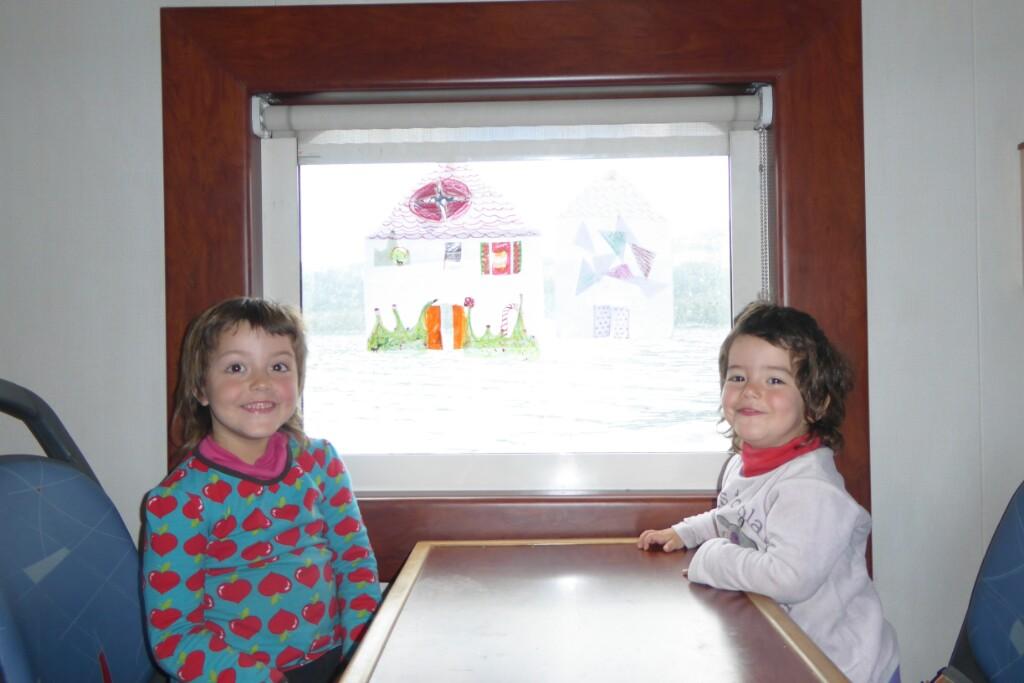 En el comedor del transbordador Jana y Bruna matan el tiempo dibujando casitas