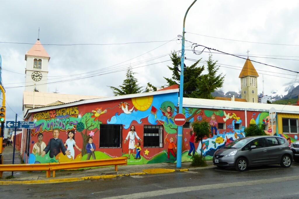 Mural colorido en la fachada de la escuela Don Bosco. El misionero también tiene un pape destacado en Ushuaia, como en Punta Arenas