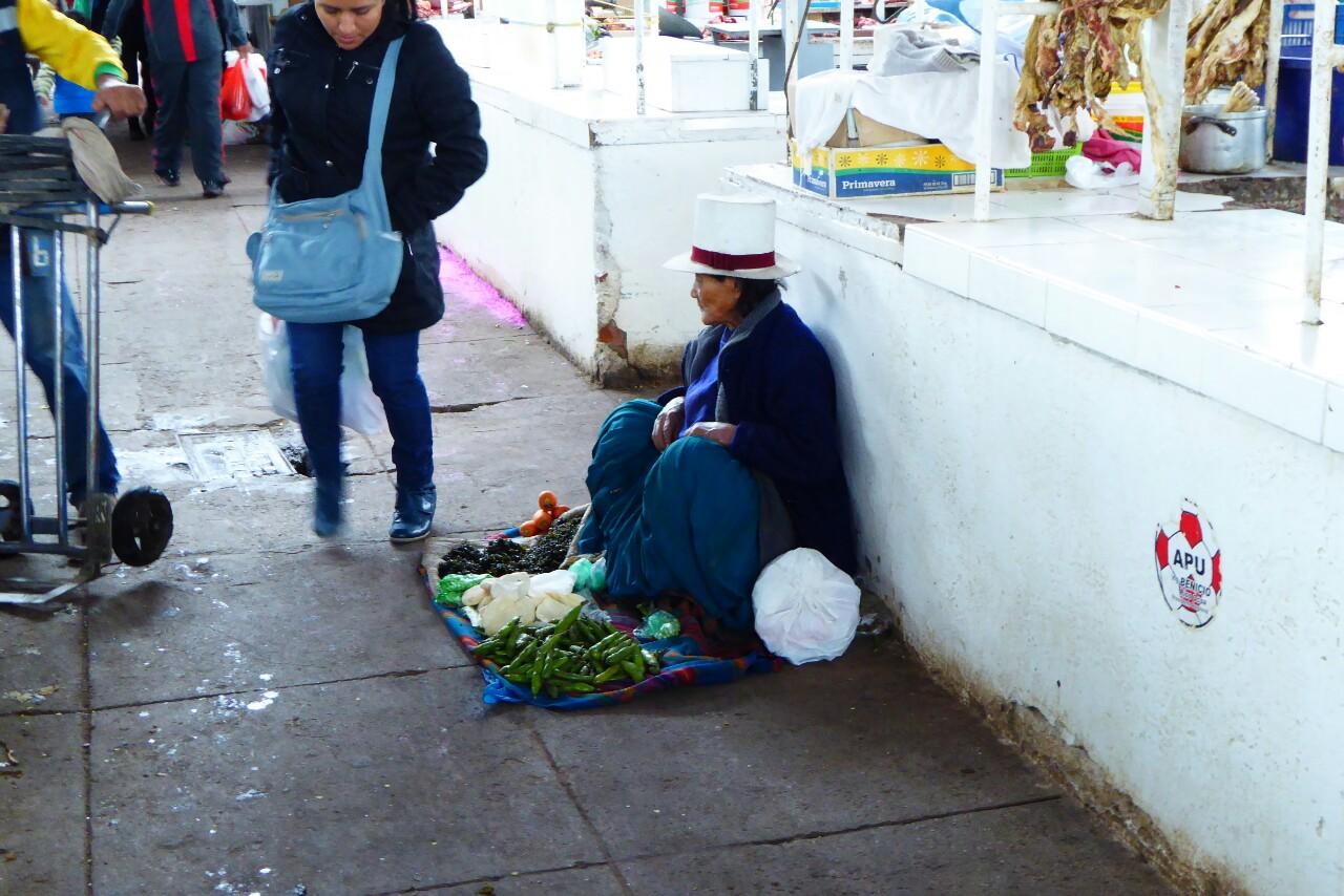 Dentro del mercado de Wanchaq, de cuclillas en el suelo, con unas pocas frutas a sus pies y un sombrero de copa blanco