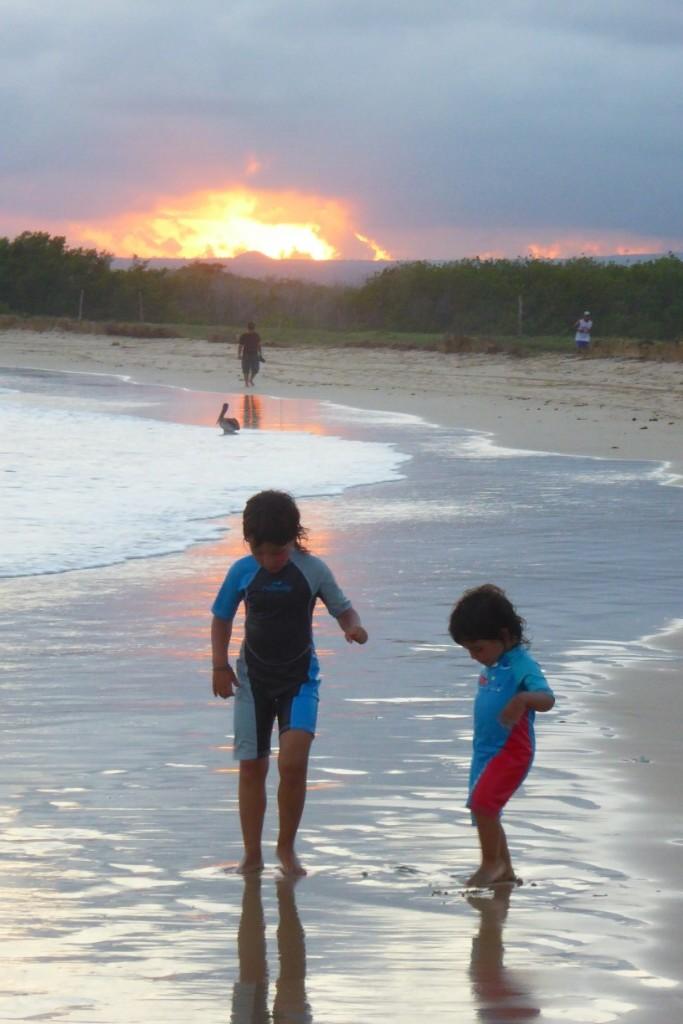Jugando en la playa a la puesta de sol
